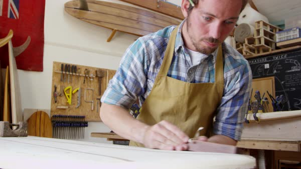 Man shaping custom surfboard in workshop shot on red camera Royalty-free stock video