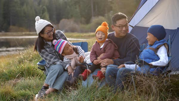 Family on a camping trip relaxing outside their tent Royalty-free stock video