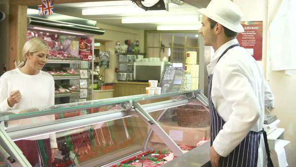 Woman asks butcher about selection of meat on display before selecting her purchase. Royalty-free stock video