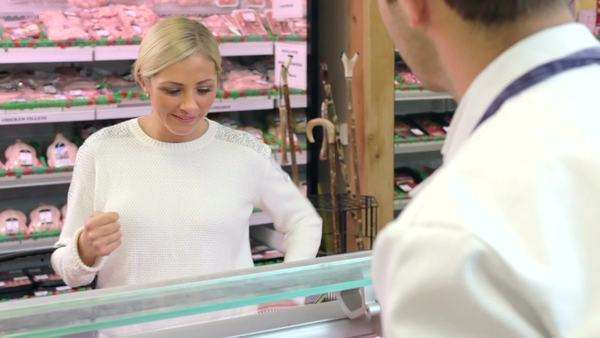 Butcher explaining to apprentice the correct way to prepare meat. Royalty-free stock video