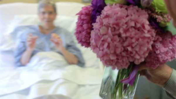 Camera follows senior man as he visits wife in hospital bed and gives her bunch of flowers. Royalty-free stock video