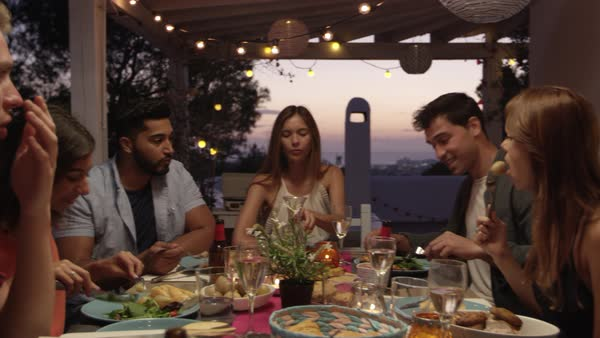 Friends talking at a dinner party on a roof terrace, Ibiza, shot on R3D Royalty-free stock video