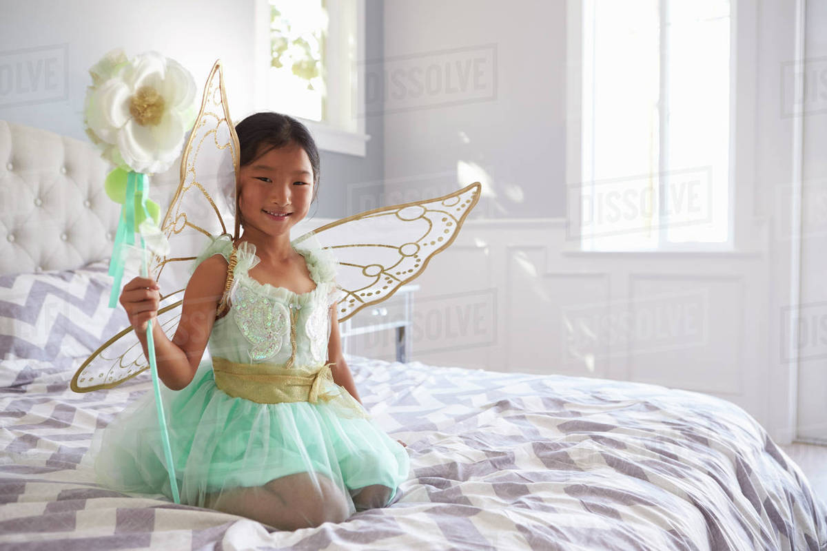Girl Dressed In Fairy Costume Sitting On Bed At Home Royalty-free stock photo