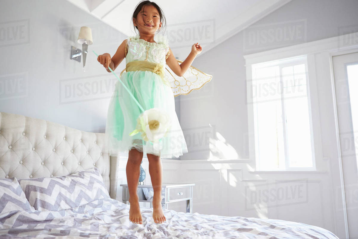Girl Dressed In Fairy Costume Jumping On Bed At Home Royalty-free stock photo