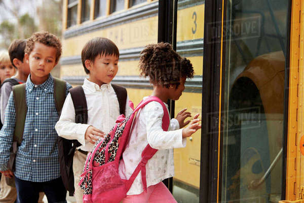 Elementary school kids climbing on to a school bus Royalty-free stock photo