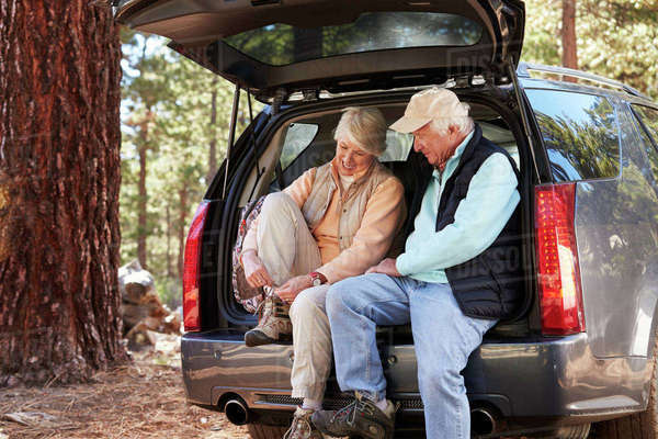 Senior couple sitting in open car trunk preparing for a hike Royalty-free stock photo