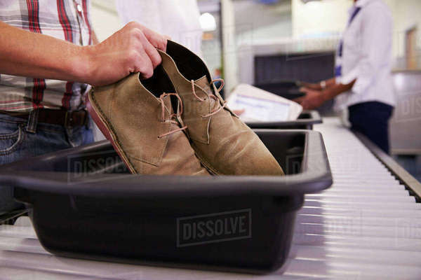 Man Putting Shoes Into Tray For Airport Security Check Royalty-free stock photo