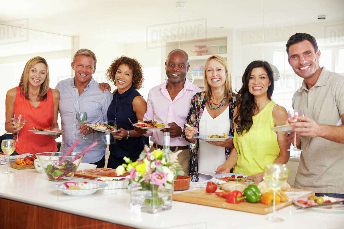 portrait of mature friends enjoying dinner party at home - stock