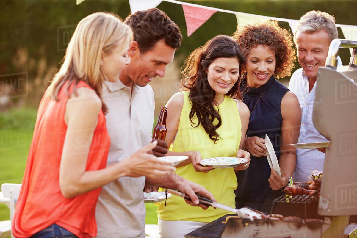 mature friends enjoying outdoor summer barbeque in garden - stock