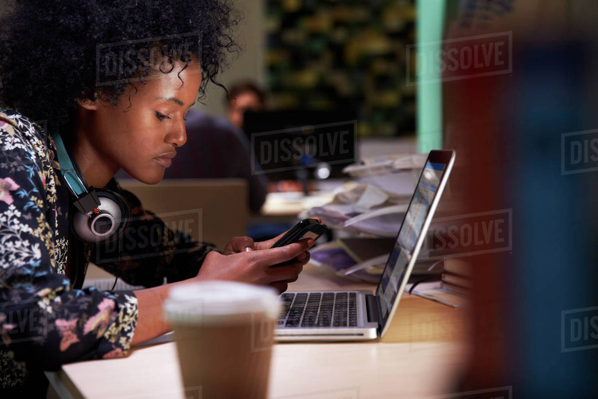 Female office worker with coffee at desk working late Royalty-free stock photo