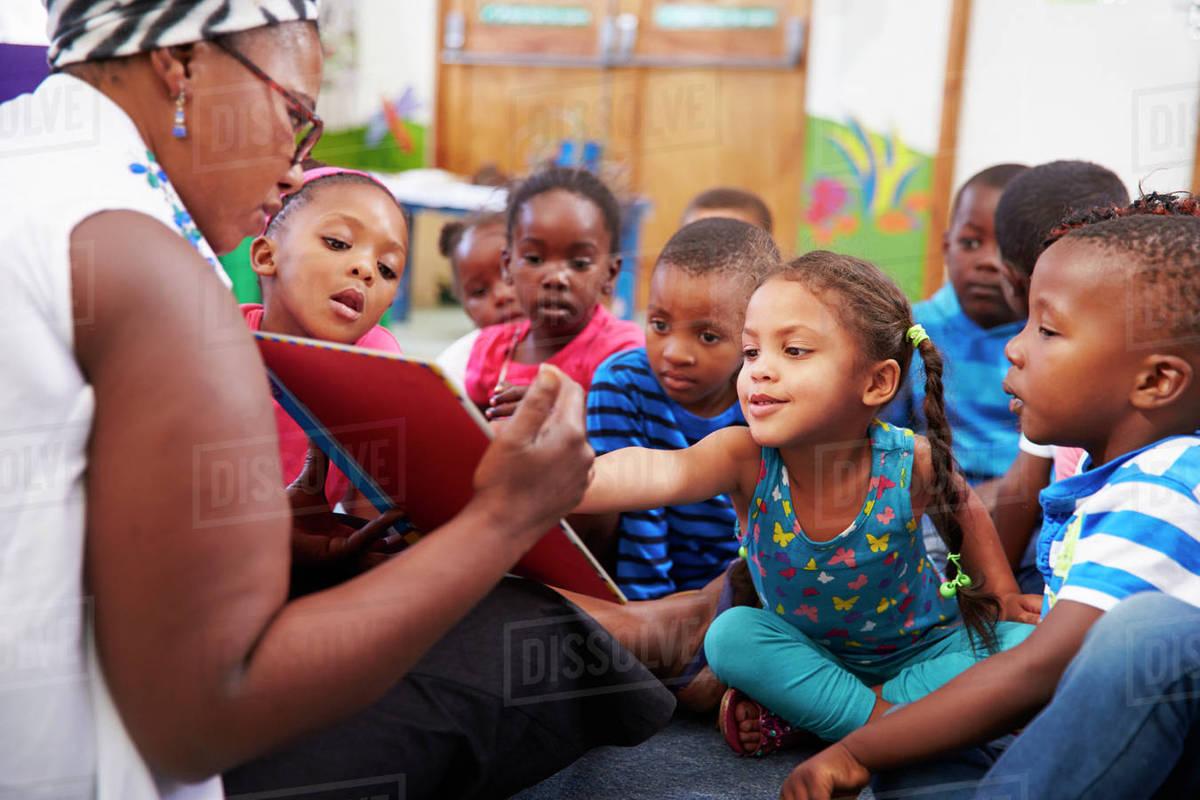 teacher reading a book with a class of preschool children stock