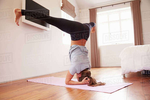 Woman doing yoga fitness exercises on mat in bedroom Royalty-free stock photo