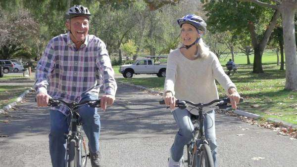 Senior couple riding bikes along country road towards camera. Royalty-free stock video