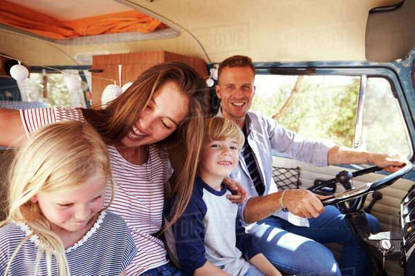 Family sitting at the front of their camper van, dad driving Royalty-free stock photo