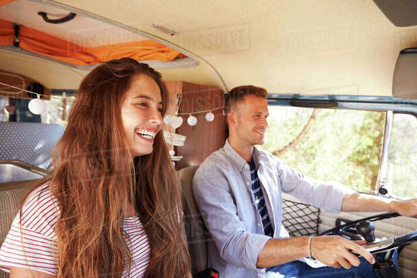 Happy couple driving a camper van on a road trip vacation Royalty-free stock photo