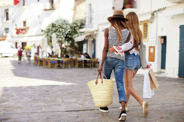 Two female friends on vacation shopping in Ibiza, back view Royalty-free stock photo