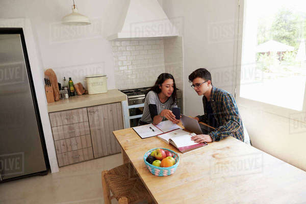 Teenagers study with laptop and phone in kitchen, elevated view Royalty-free stock photo