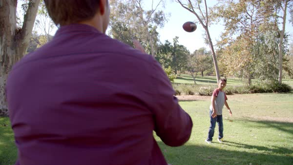 Seven year old boy throwing football with his dad in park Royalty-free stock video