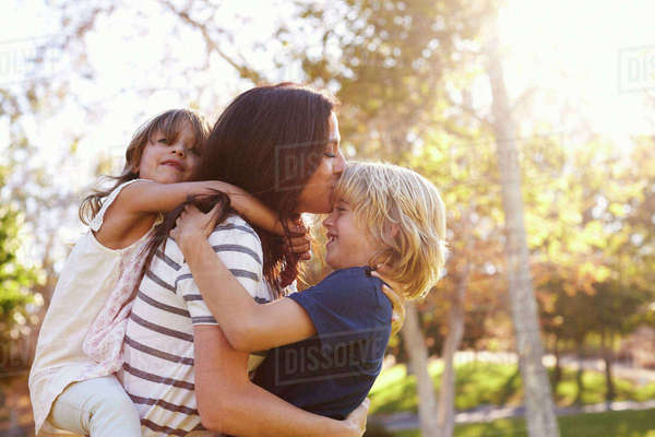 Mother carrying son and daughter as they play in park Royalty-free stock photo