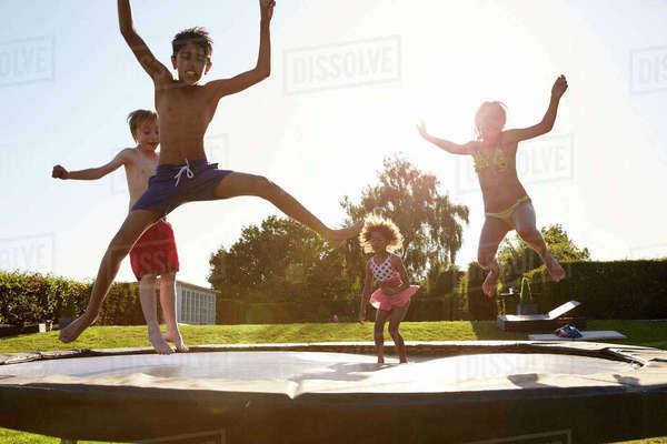 Group of children having fun jumping on outdoor trampoline Royalty-free stock photo