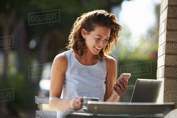 Young woman using smartphone and laptop outside a cafe Royalty-free stock photo