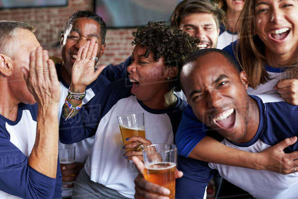 Portrait of friends watching game in sports bar on screens  Royalty-free stock photo
