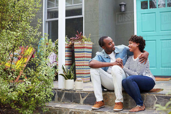 Young couple sit looking at each other outside their house Royalty-free stock photo