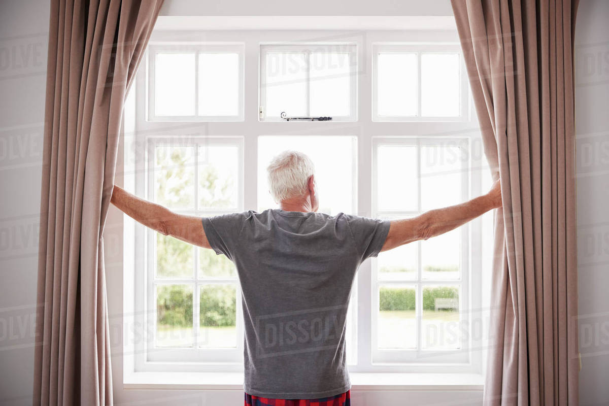 Senior Man Opening Bedroom Curtains And Looking Out Of Window stock photo
