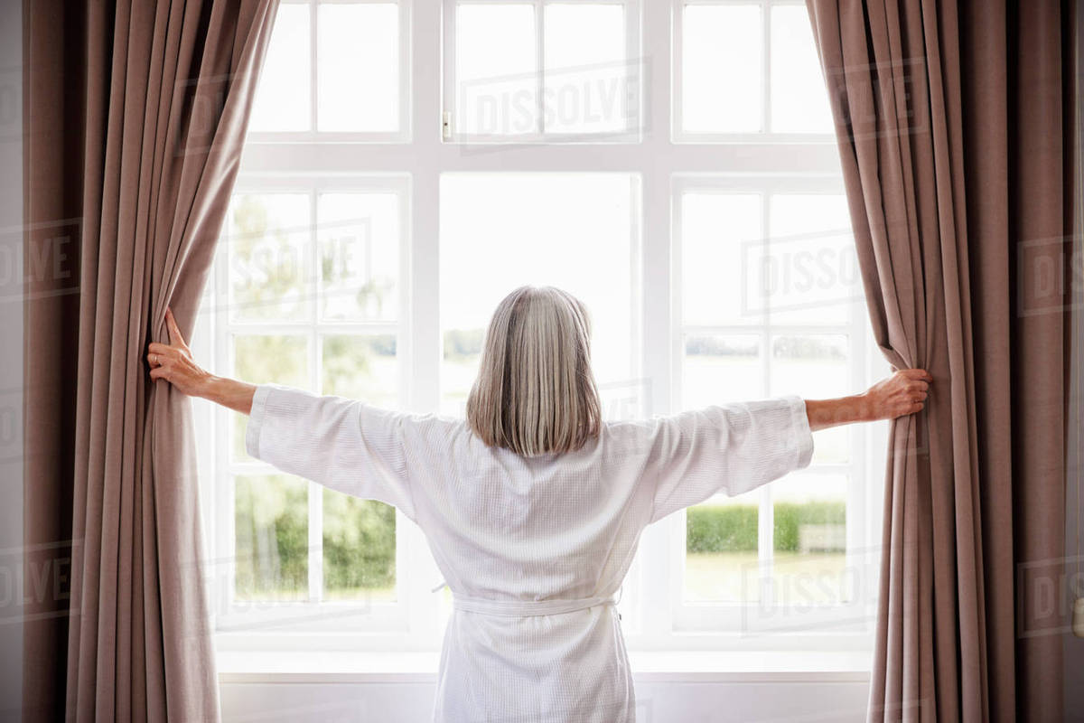 Senior Woman Opening Bedroom Curtains And Looking Out Of Window stock photo