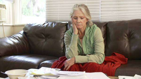 Upset senior woman sits on sofa under blanket, looking at bills and shaking her head in despair. Royalty-free stock video