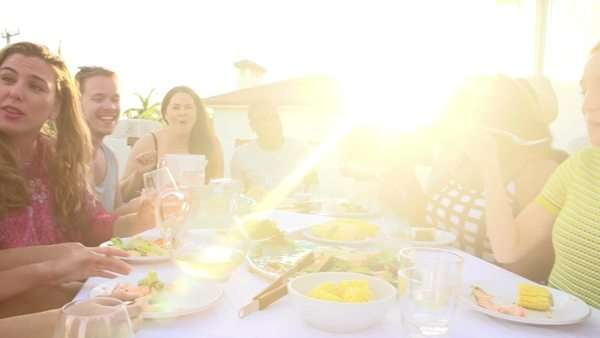 Camera tracks around group of young people sitting around table outdoors enjoying meal together. Royalty-free stock video