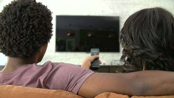 Looking over couple's shoulder as they sit on sofa and watch television together. Royalty-free stock video