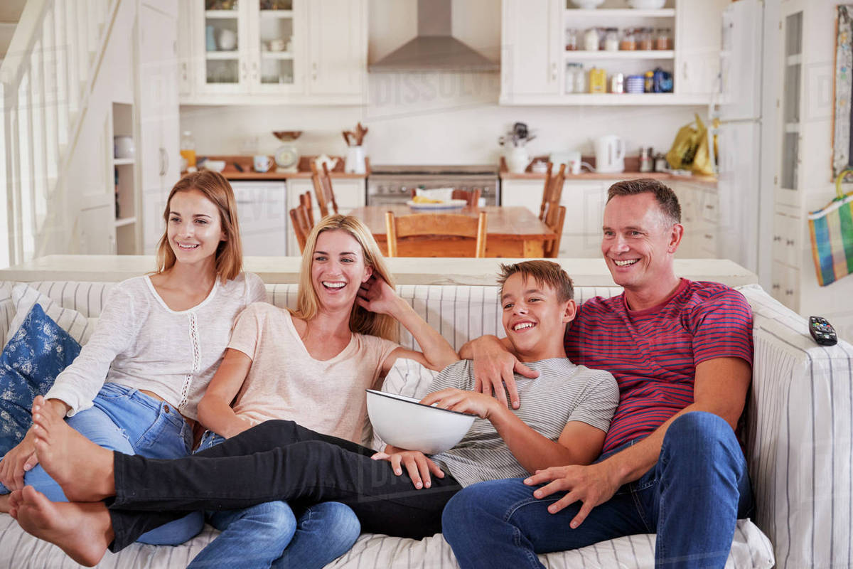 Family With Teenage Children Sitting On Sofa Watching TV Together