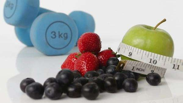 Selection of fresh fruit and had set of hand weights appear in frame - tape measure moves across them Royalty-free stock video