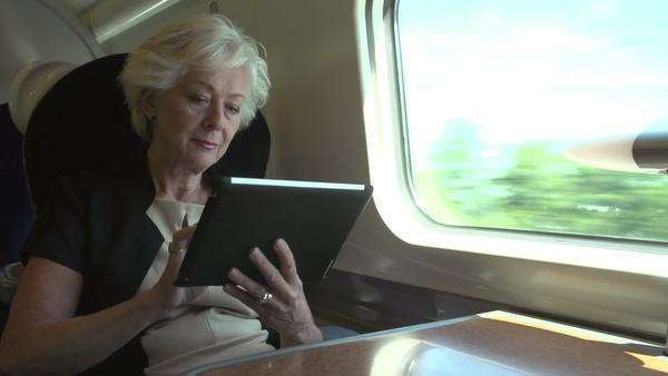Senior businesswoman sitting at table working using digital tablet. Royalty-free stock video