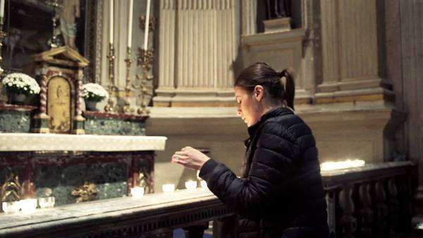 Woman praying, lit candle in the church Royalty-free stock video