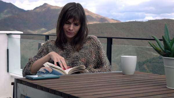 Woman reading book by table on terrace Royalty-free stock video