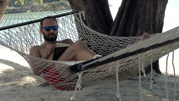 Man reading book while lying on hammock on beach Royalty-free stock video