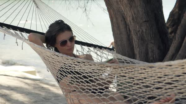 Woman reading book lying on hammock on beach Royalty-free stock video