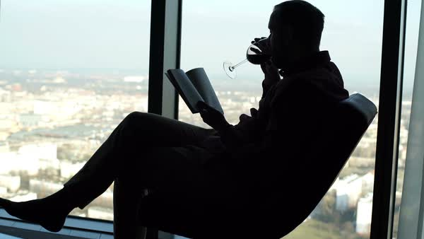 Silhouette of young man reading book on chair by window Royalty-free stock video