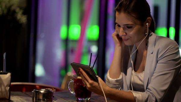 Young, pretty woman watching movie on smartphone sitting in cafe at night Royalty-free stock video