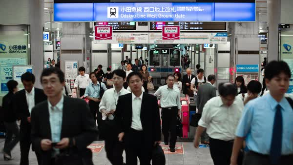 People passing through subway turnstile, train arriving on platform in background in Tokyo Royalty-free stock video