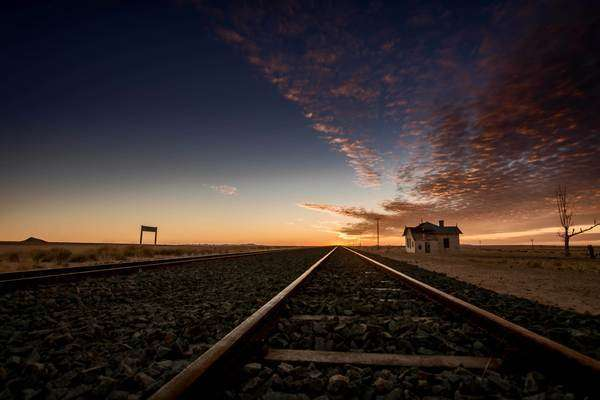 Wide shot of the sun disappearing below the horizon on the vanishing point of a railroad Rights-managed stock video