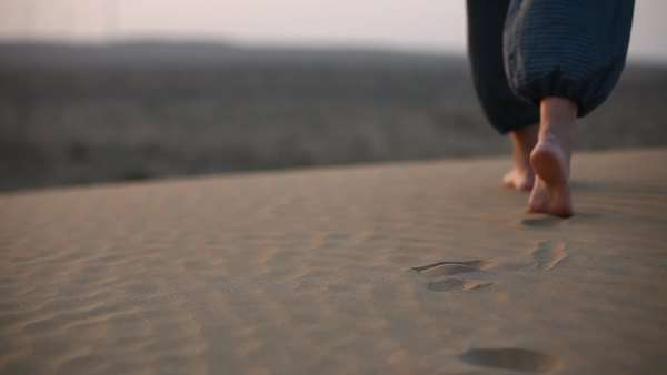 Medium shot of a person walking in the sand Royalty-free stock video