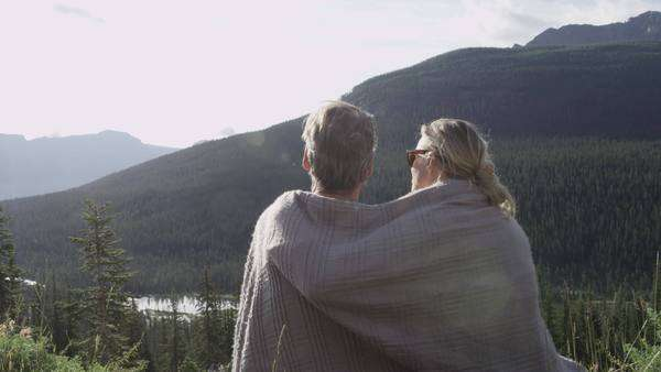 Medium shot of couple sitting under a blanket in the mountains Royalty-free stock video
