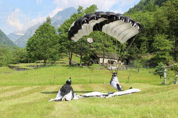 Wingsuit flyers landing in a field in Ticino canton, Switzerland Royalty-free stock photo