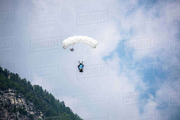 Wingsuit flyer gliding above a mountain in Ticino canton, Switzerland Royalty-free stock photo