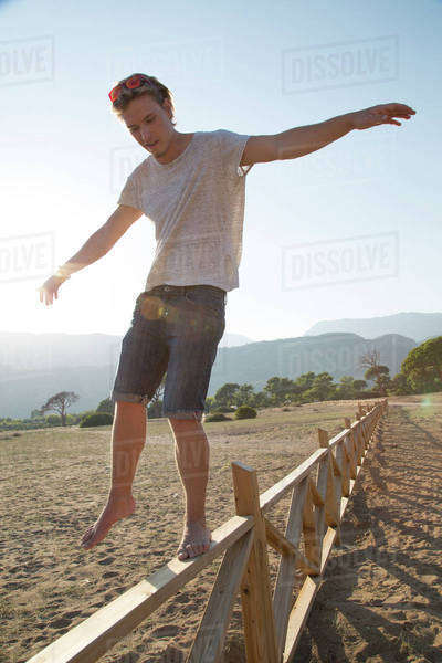 Man balancing on a wooden fence Royalty-free stock photo