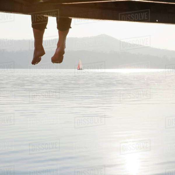 Man dangling his legs from a pier Royalty-free stock photo