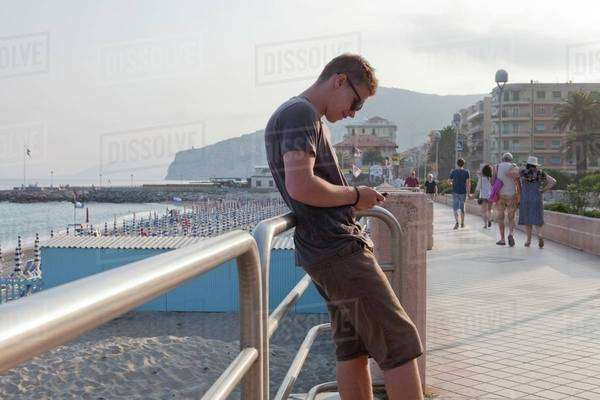 Young man using mobile phone on the coast of Liguria, Italy Royalty-free stock photo